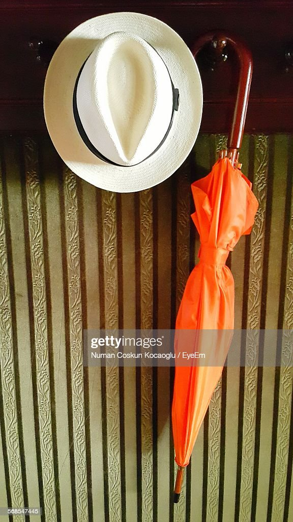 High Angle View Of Orange Umbrella And Hat Hanging Against Wall : Stock Photo