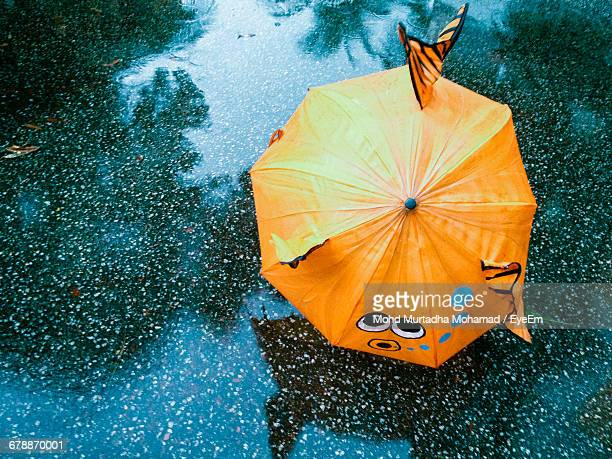 High Angle View Of Orange Umbrella On Wet Footpath During Rain