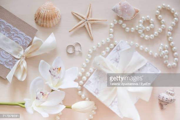 High Angle View Of Orchid With Seashells By Gifts And Personal Accessories On Table
