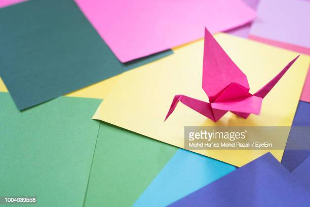 high angle view of origami on colorful papers - origami foto e immagini stock
