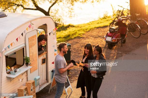High angle view of owner looking at customers standing on street through food truck window