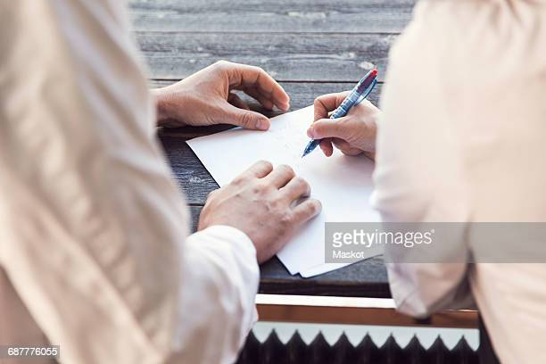 High angle view of owners doing paperwork in grocery store