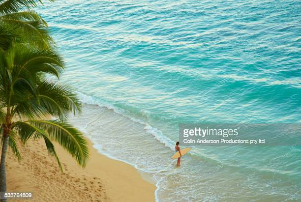 high angle view of pacific islander woman carrying surfboard on beach - isole hawaii foto e immagini stock