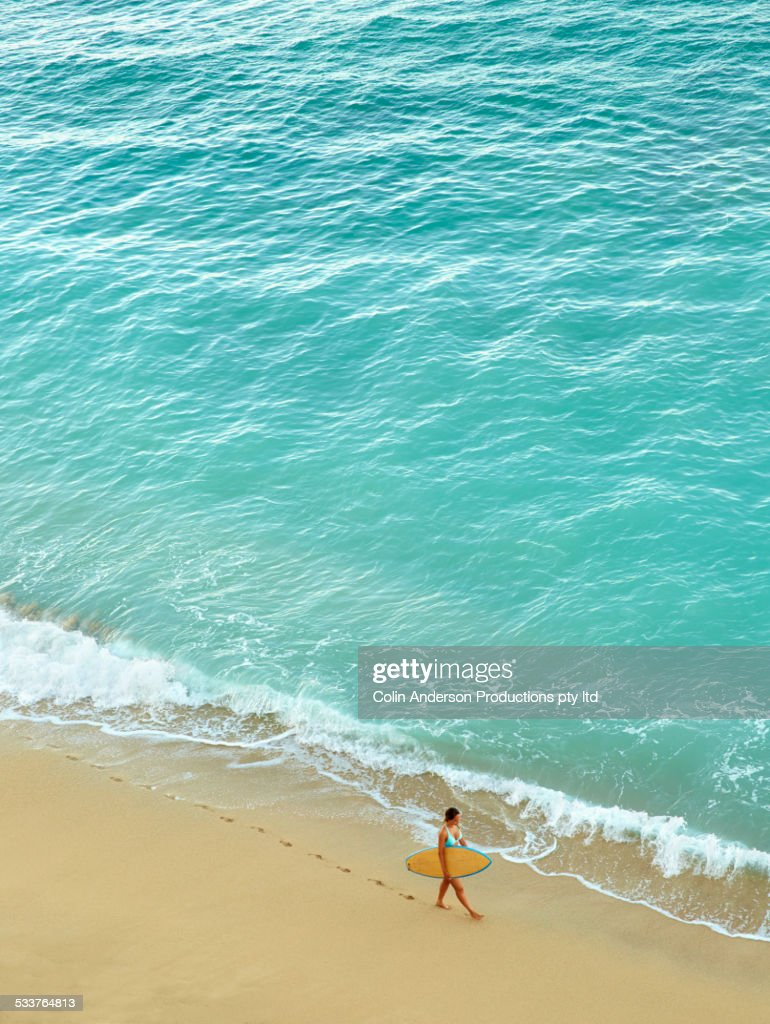 High angle view of Pacific Islander woman carrying surfboard on beach : Foto stock