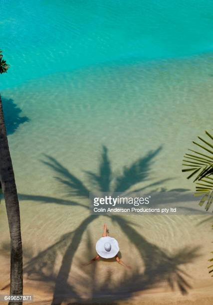 High angle view of Pacific Islander woman laying in ocean