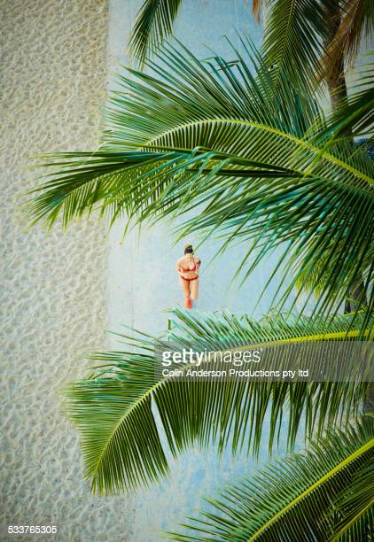 High angle view of Pacific Islander woman running on sidewalk near beach