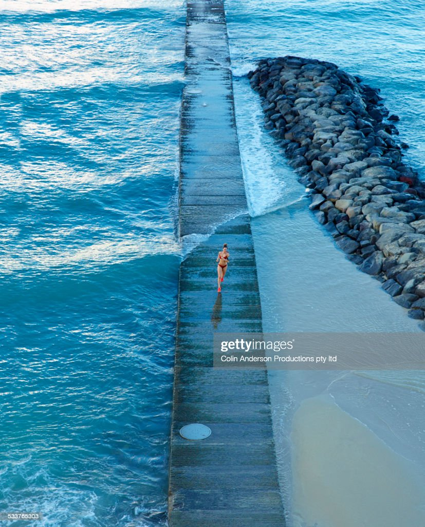High angle view of Pacific Islander woman running on wooden pier on beach : Foto stock