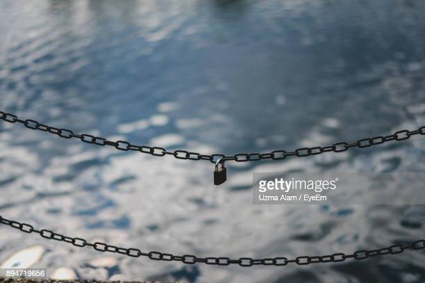 High Angle View Of Padlock Hanging On Chain Against River