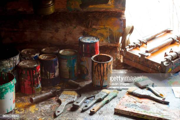 High angle view of paint cans with paintbrushes on wooden table