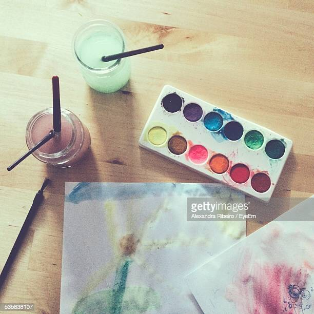 High Angle View Of Paintbrushes And Palette With Paper On Table