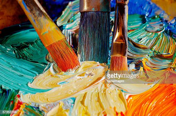 high angle view of paintbrushes mixing paint on a palette - paleta de cores imagens e fotografias de stock