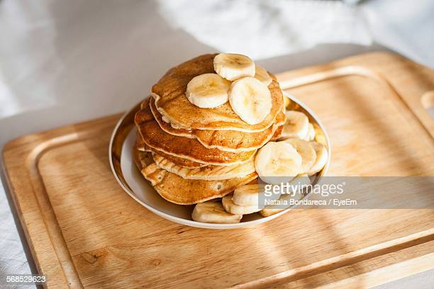 high angle view of pancakes with banana in plate on table - pancake stock pictures, royalty-free photos & images