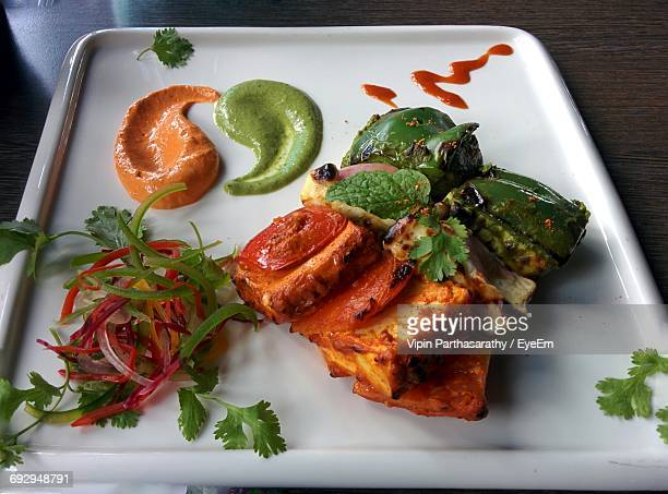 High Angle View Of Paneer Tikka Served With Salad And Chutney In Plate On Table