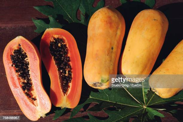 high angle view of papayas with leaves on table - papaya stock photos and pictures