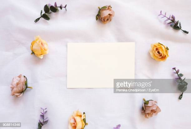 High Angle View Of Paper Amidst Various Flowers On Pink Fabric