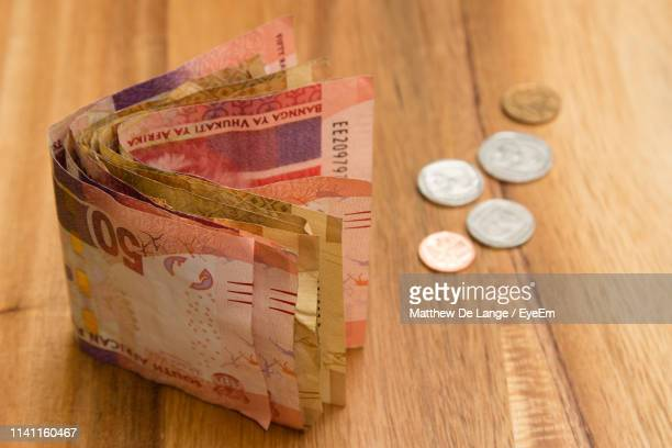 high angle view of paper currencies and coins on wooden table - south african currency stock pictures, royalty-free photos & images