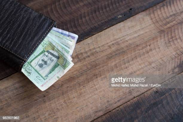 High Angle View Of Paper Currency In Wallet On Wooden Table