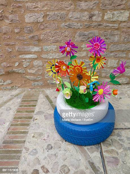 High Angle View Of Paper Flowers And Abandoned Tires Decoration