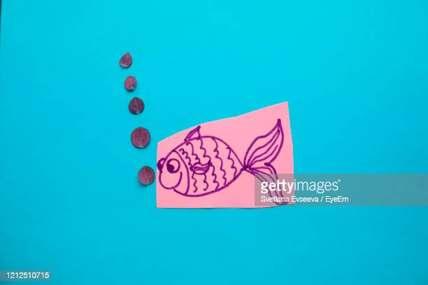 high angle view of paper painting on blue background - poisson avril photos et images de collection