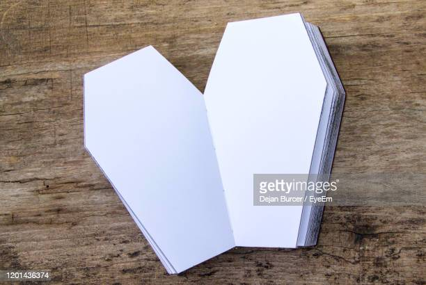 high angle view of papers stack in coffin cut outs on table - open casket stock pictures, royalty-free photos & images