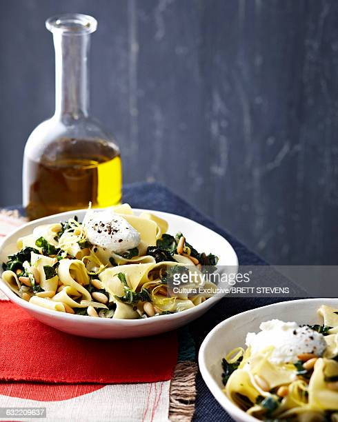 High angle view of pappardelle with chard in bowls and decanter of olive oil