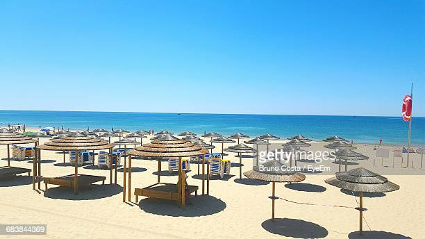 high angle view of parasols at beach against clear blue sky - algarve fotografías e imágenes de stock