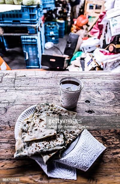 High Angle View Of Paratha Served In Plate By Drink On Table