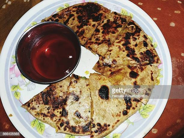 High Angle View Of Paratha With Sauce Served In Plate On Table