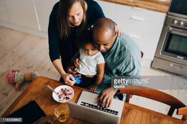 high angle view of parents with daughter shopping online on laptop at dining room - adulte d'âge moyen photos et images de collection