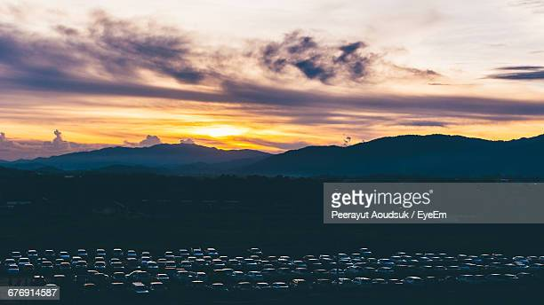 High Angle View Of Parked Cars Against Mountains During Sunset