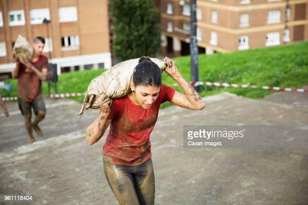 high angle view of participants carrying sandbag and climbing steps during race - sandbag stock pictures, royalty-free photos & images