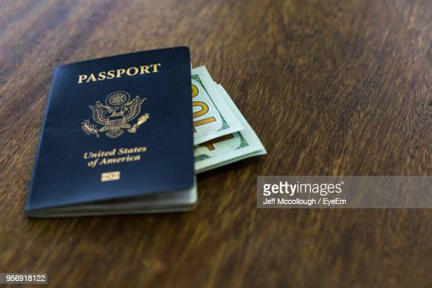 High Angle View Of Passport With Currency On Wooden Table