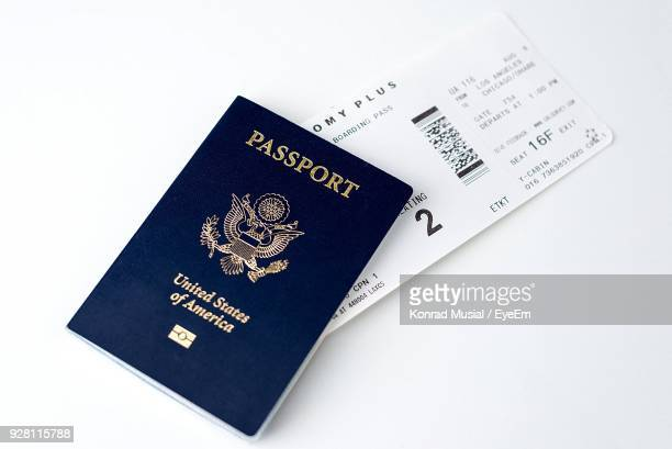 high angle view of passport with ticket over white background - passeport photos et images de collection