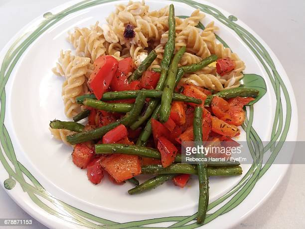 high angle view of pasta and vegetables served on table - rebecca haertel stock-fotos und bilder