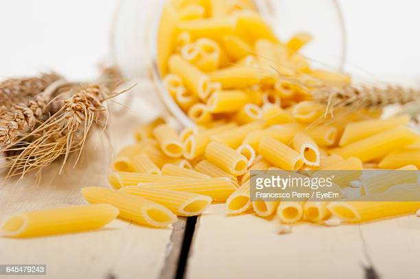 High Angle View Of Pasta And Wheat On Wooden Table