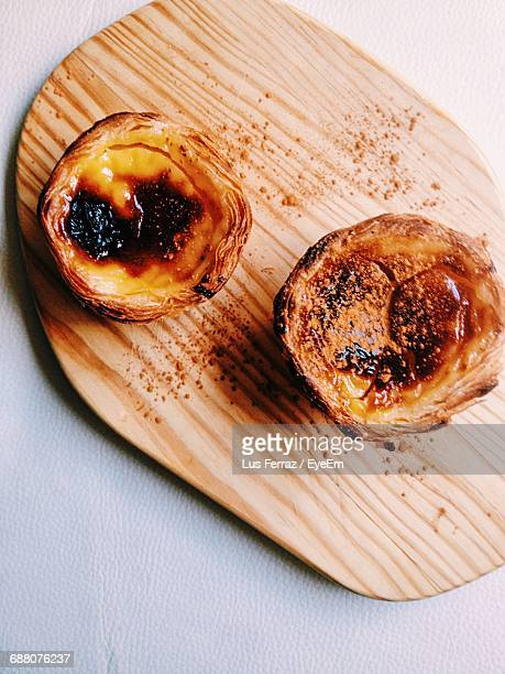 High Angle View Of Pastel De Nata On Cutting Board At Table