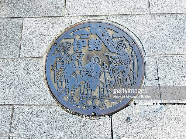 High Angle View Of Patterned Manhole Lid On Street