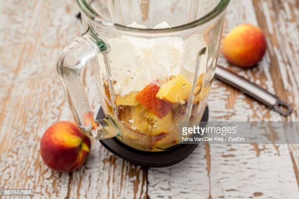 High Angle View Of Peaches And Banana In Container On Wooden Table