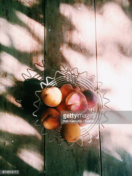 High Angle View Of Peaches In Metallic Bowl On Wooden Table
