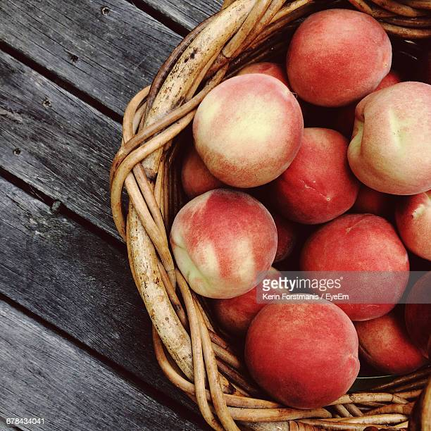 High Angle View Of Peaches In Wicker Basket On Table