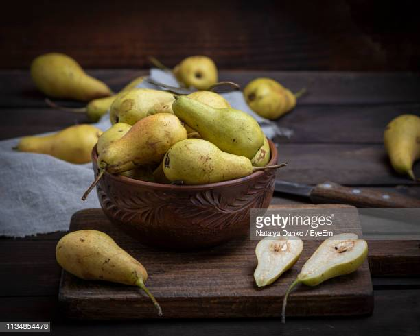 high angle view of pears in bowl on wooden table - pear stock pictures, royalty-free photos & images