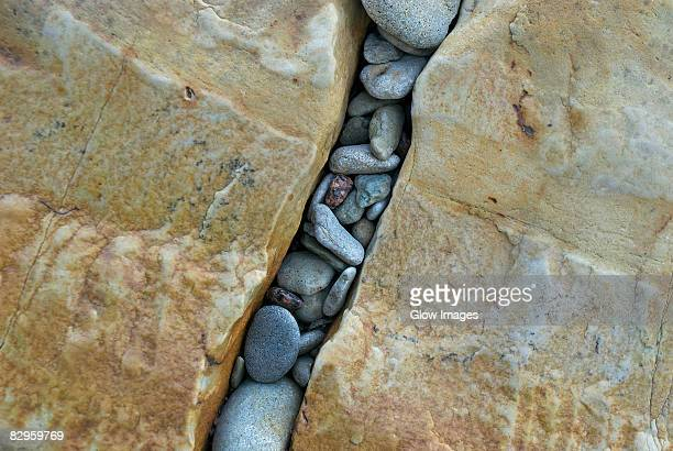 High angle view of pebbles in a gap of rocks