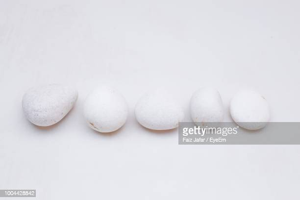 high angle view of pebbles in row over white background - kiesel stock-fotos und bilder