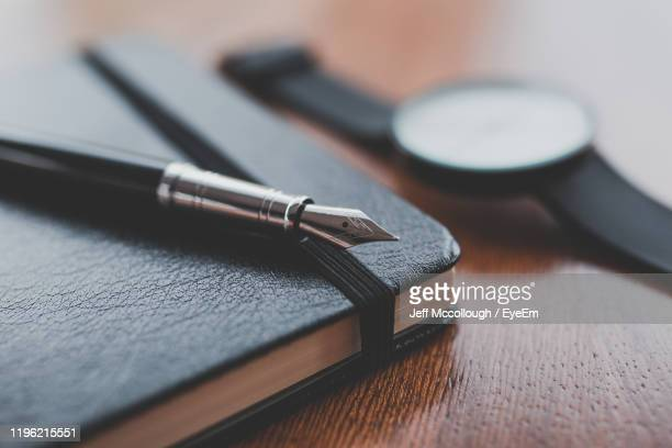 high angle view of pen and book on table - publication stock pictures, royalty-free photos & images