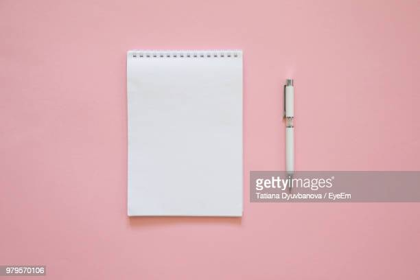 high angle view of pen and book over pink background - stift stock-fotos und bilder