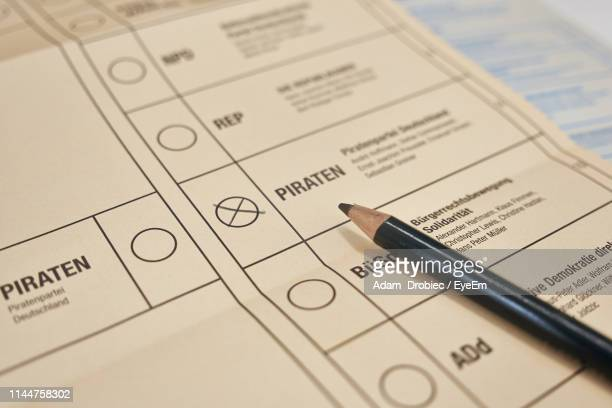 high angle view of pen and checklist on table - election stock-fotos und bilder