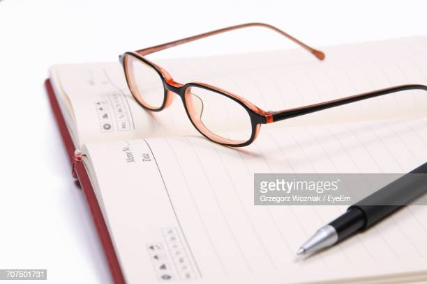 High Angle View Of Pen And Eyeglasses On Diary Over White Background