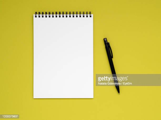 high angle view of pen and notebook on yellow background - spiral notebook stock pictures, royalty-free photos & images