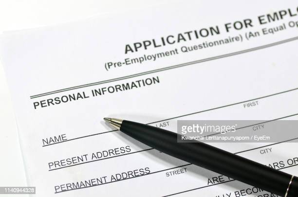 high angle view of pen on application form - application form stock pictures, royalty-free photos & images