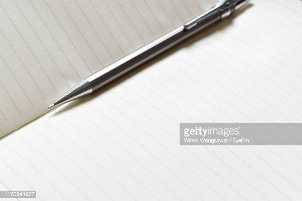 high angle view of pen on book - wimol wongsawat stock photos and pictures
